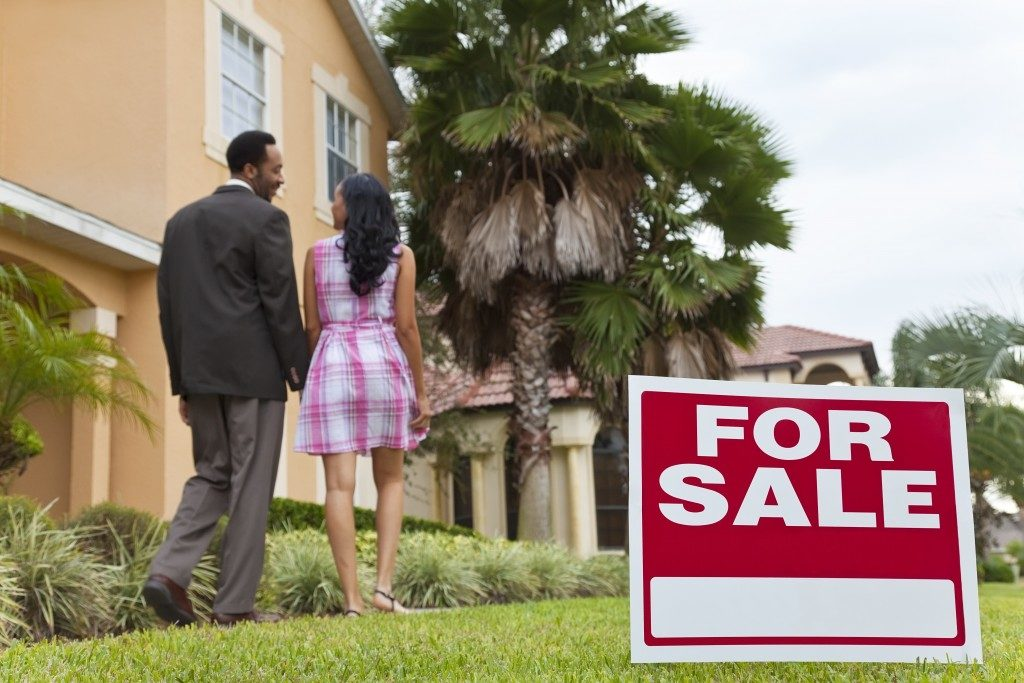 Couple talking in front of house for sale
