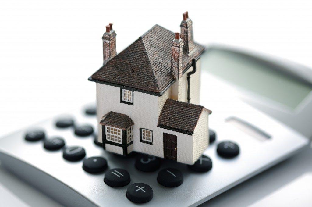 a miniature house and a calculator