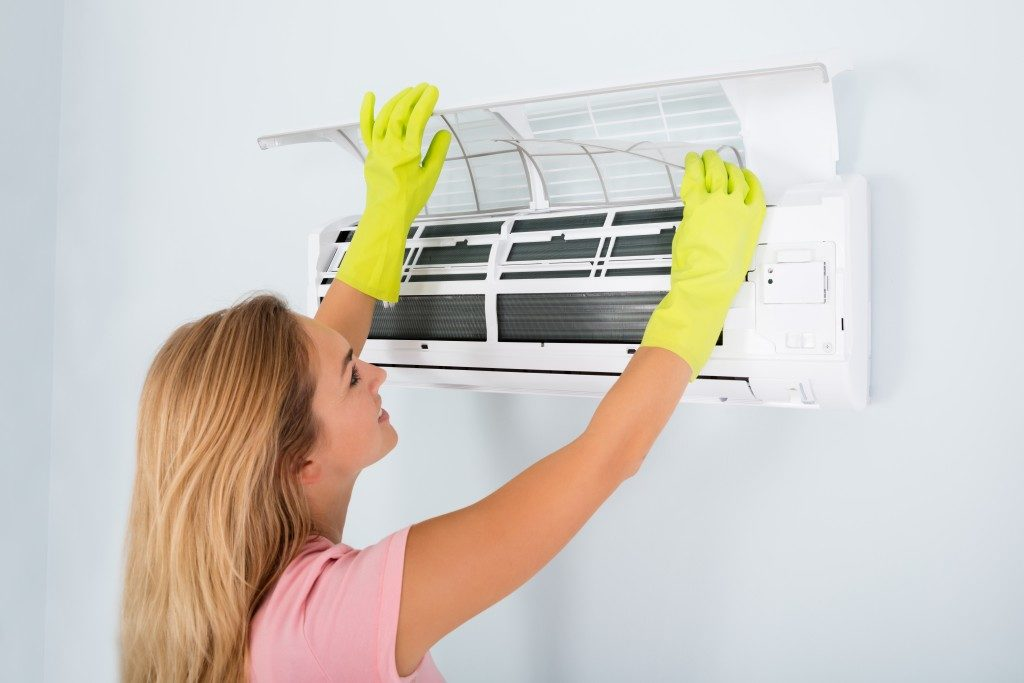woman cleaning aircon
