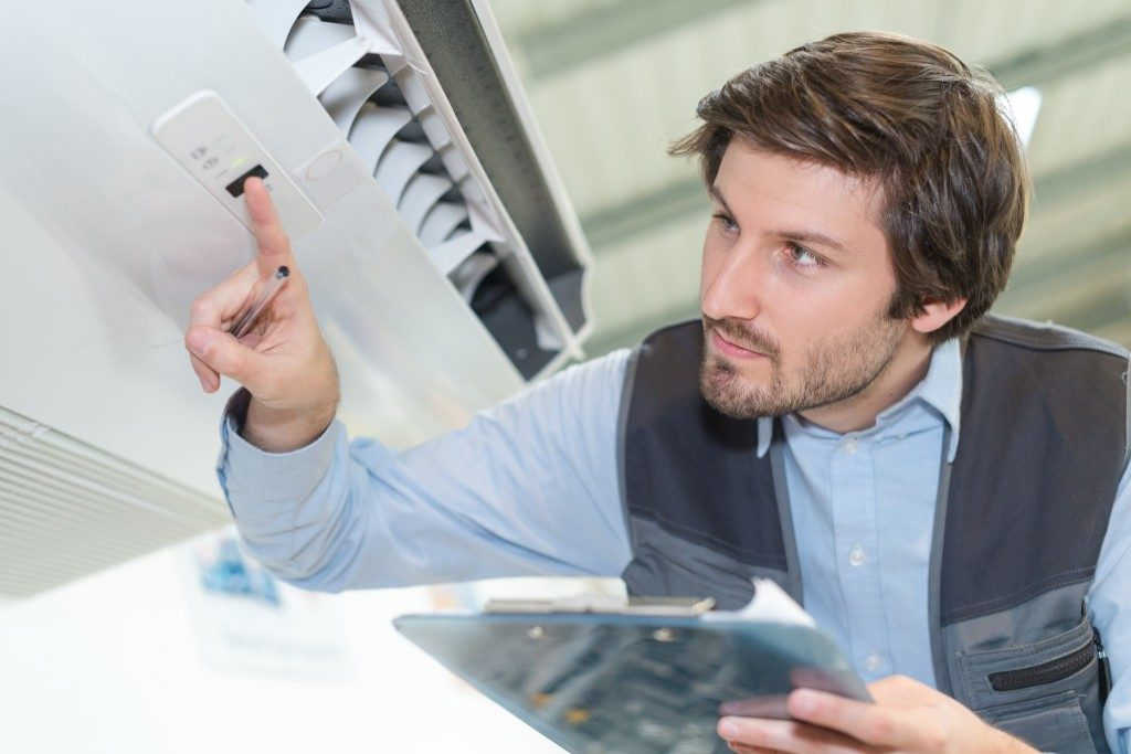 man pushing buttons of airconditioner