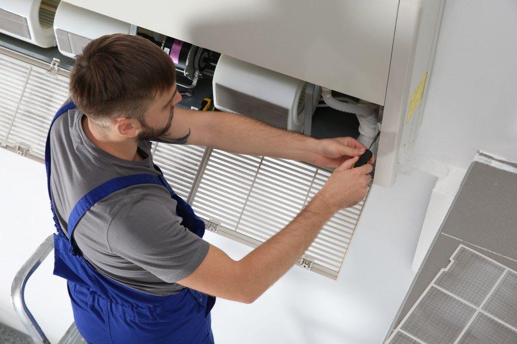 man installing a ventilation system