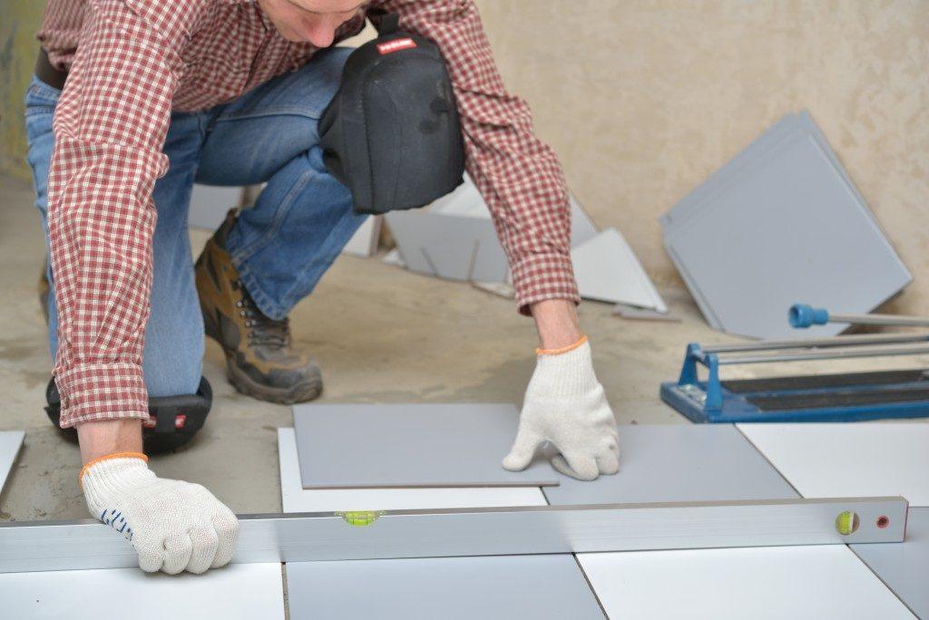 man attaching floor tiles