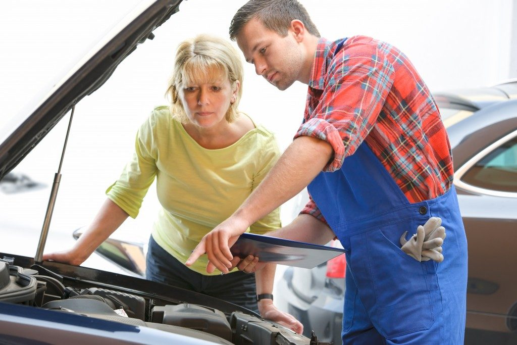 Auto mechanic and car owner looking at the engine