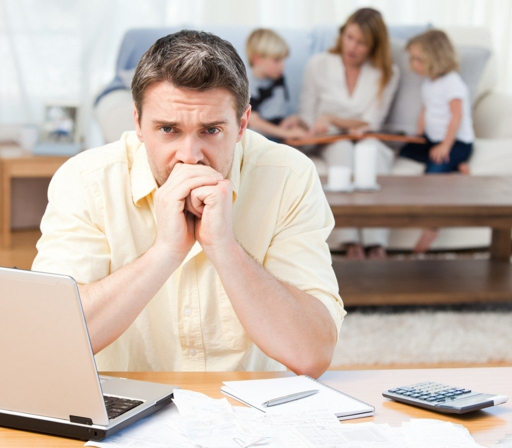 Man worried about bills with family in the background