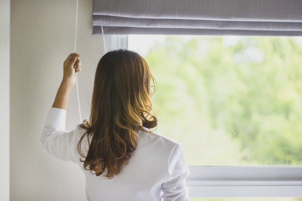 woman pulling a window blind