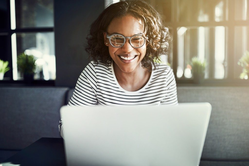 woman smiling while doing her work on a laptop