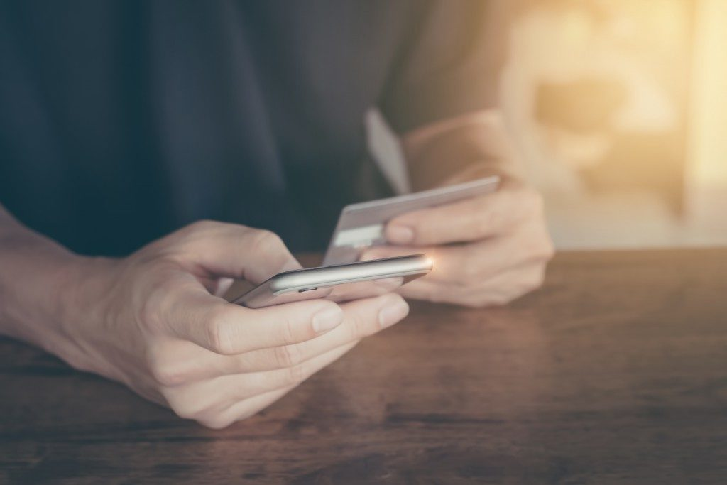 a person using his credit card to pay online in his phone