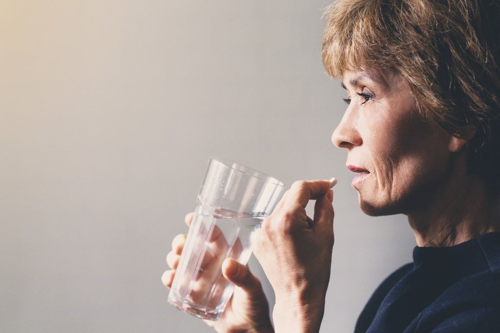 Employee taking in medicine with water