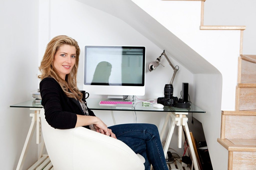 Young professional photographer working from home and sitting at her desk at home