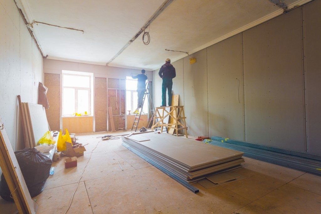 Workers installing plasterboard walls