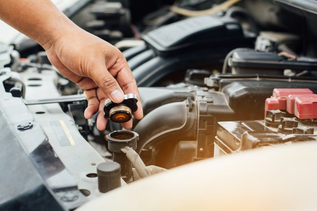 hand of a person closing the container at the car's engine after changing the transmission fluid