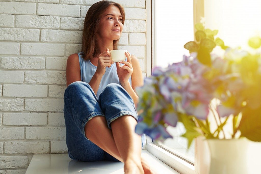 inspired woman relaxing on window ledge