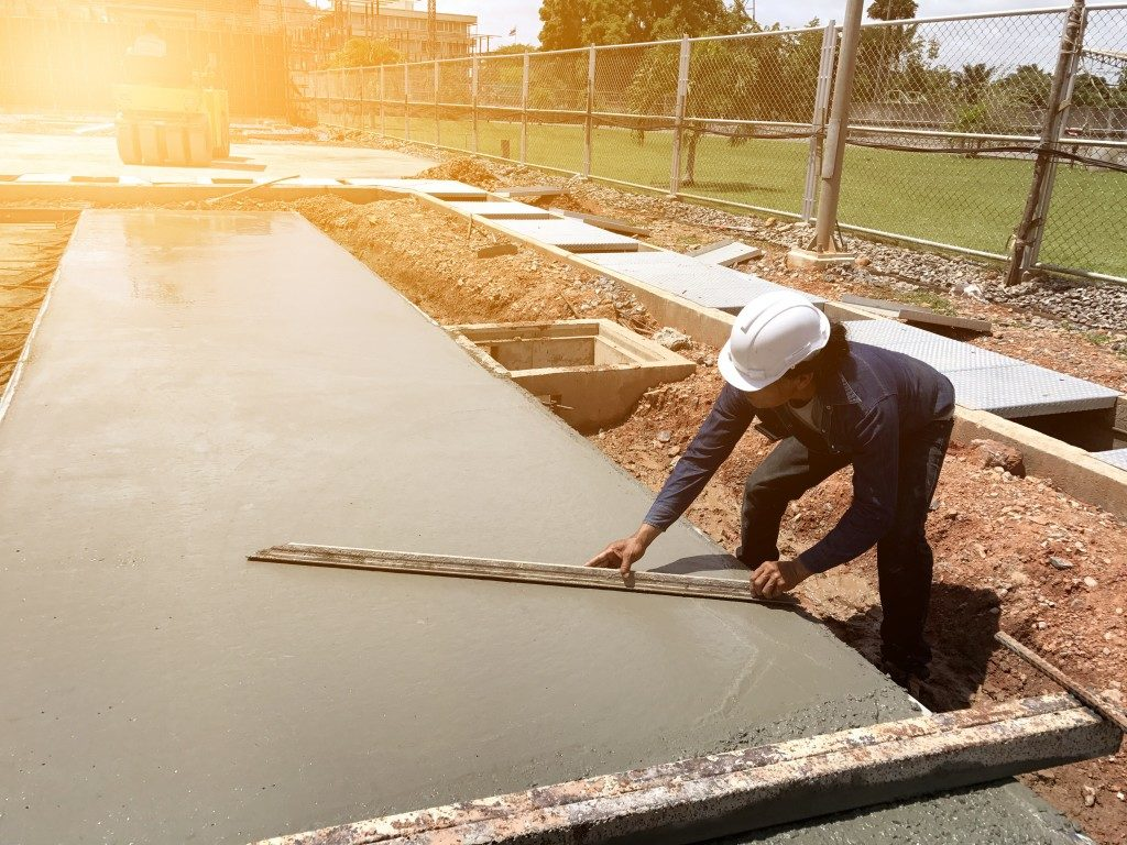 Worker spreading concrete mix construction