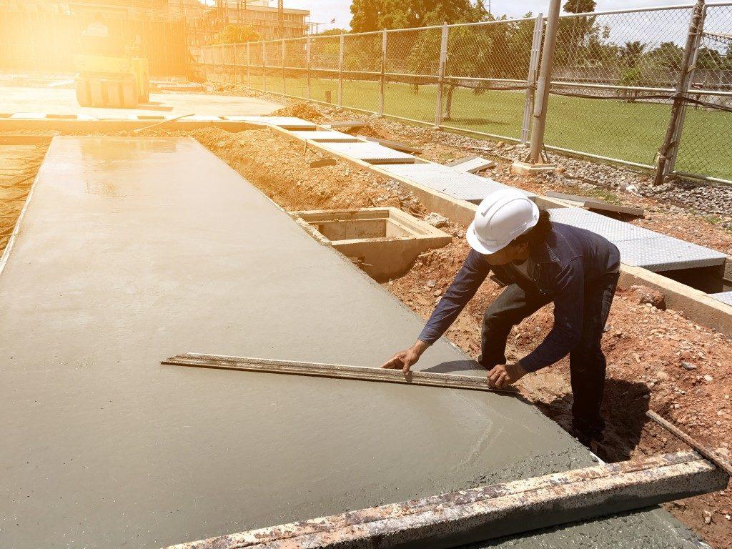 Worker spreading concrete mix construction