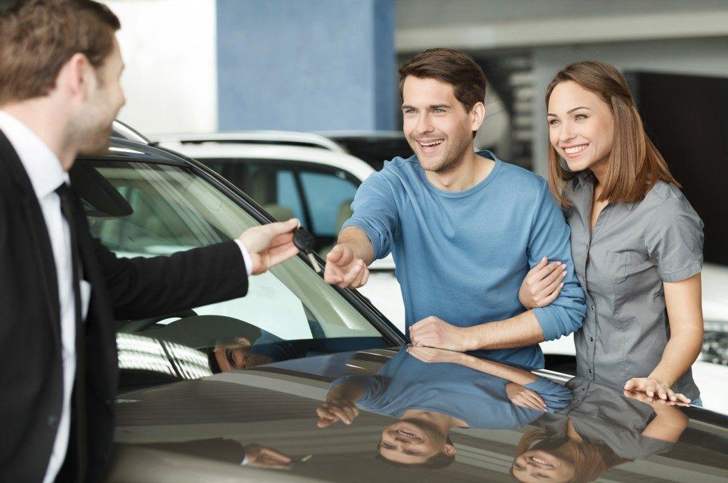 car dealer giving a couple the keys to the car