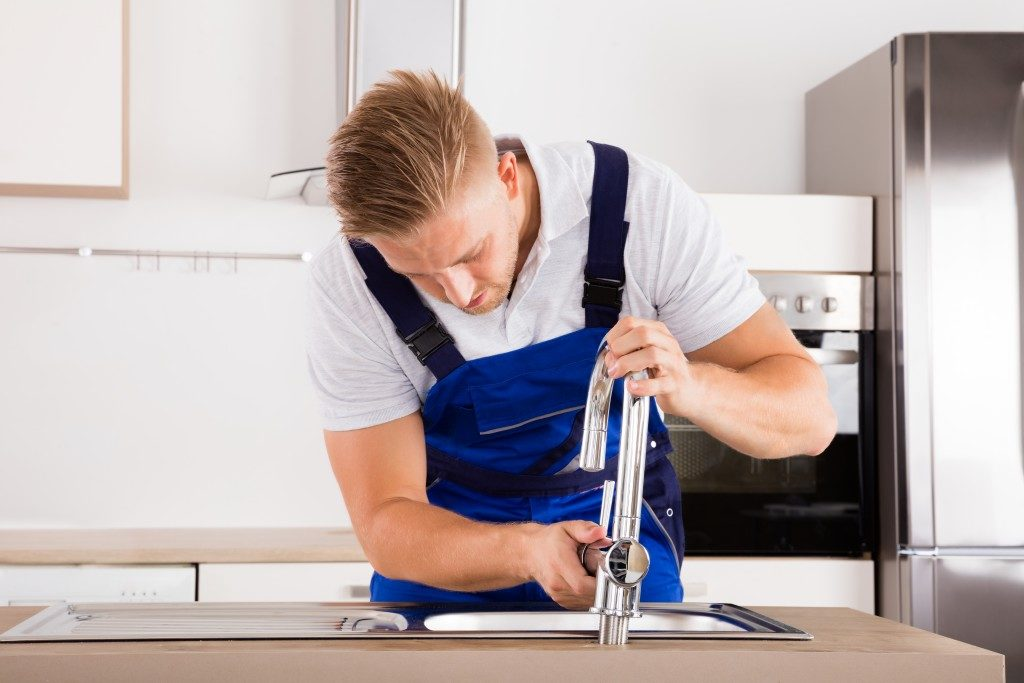 Man installing new sink faucet in the kitchen
