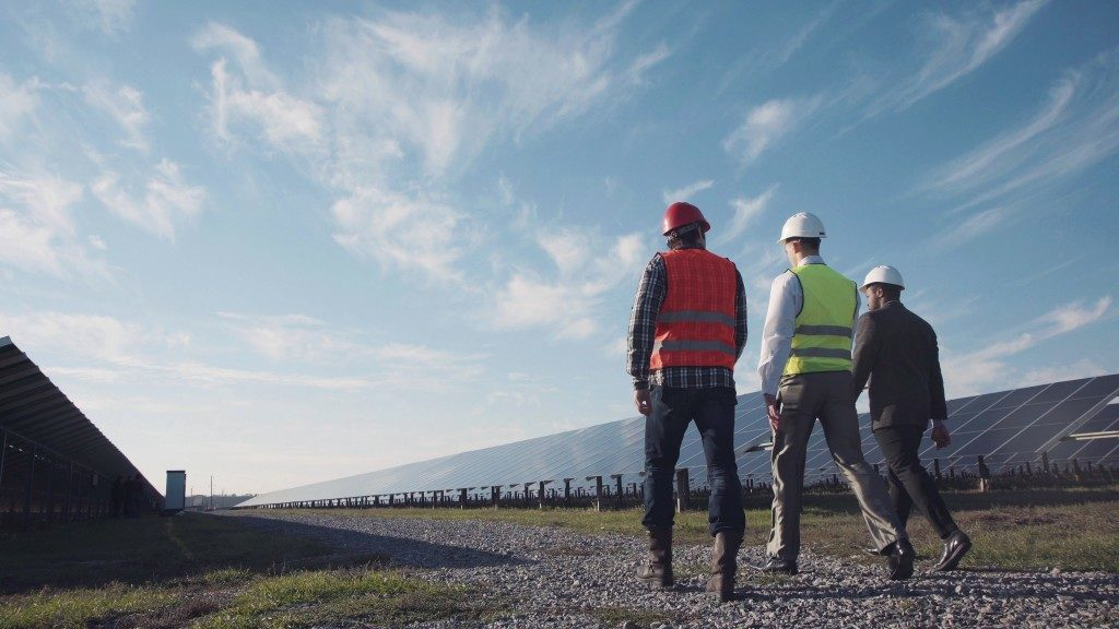 Workers and investor through solar power field