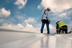Men on top of single ply roofing