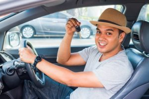 Man holding out keys to new car
