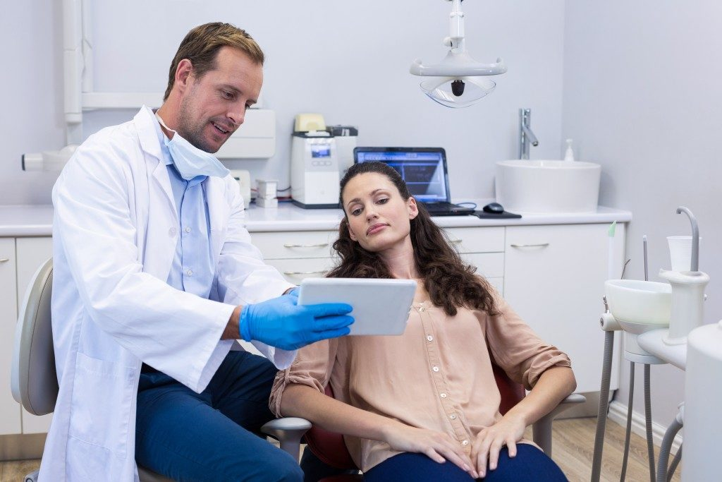 dentist discussing some information with his patient