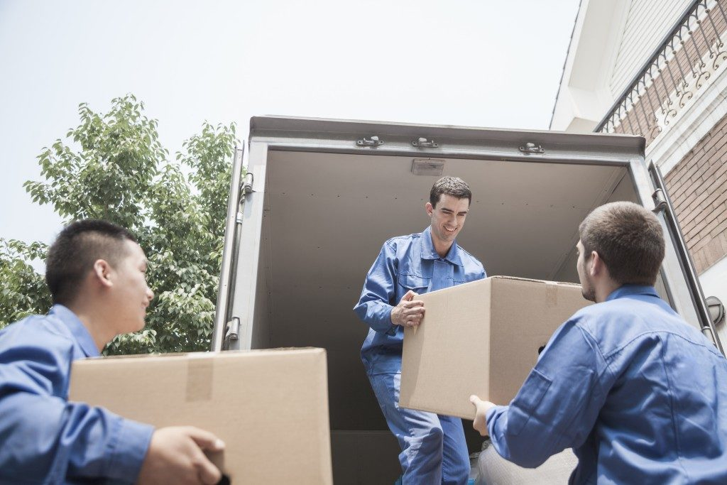 Moving company loading boxes into a truck