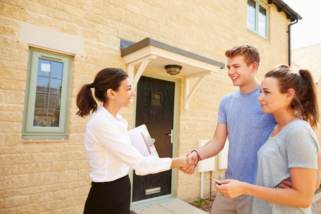 Couple shaking hands with broker of house