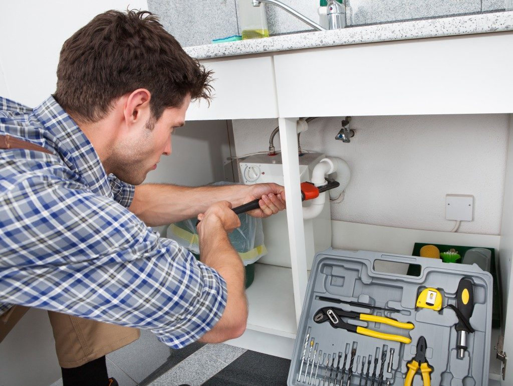 Plumber Working With Pipe Wrench In Kitchen