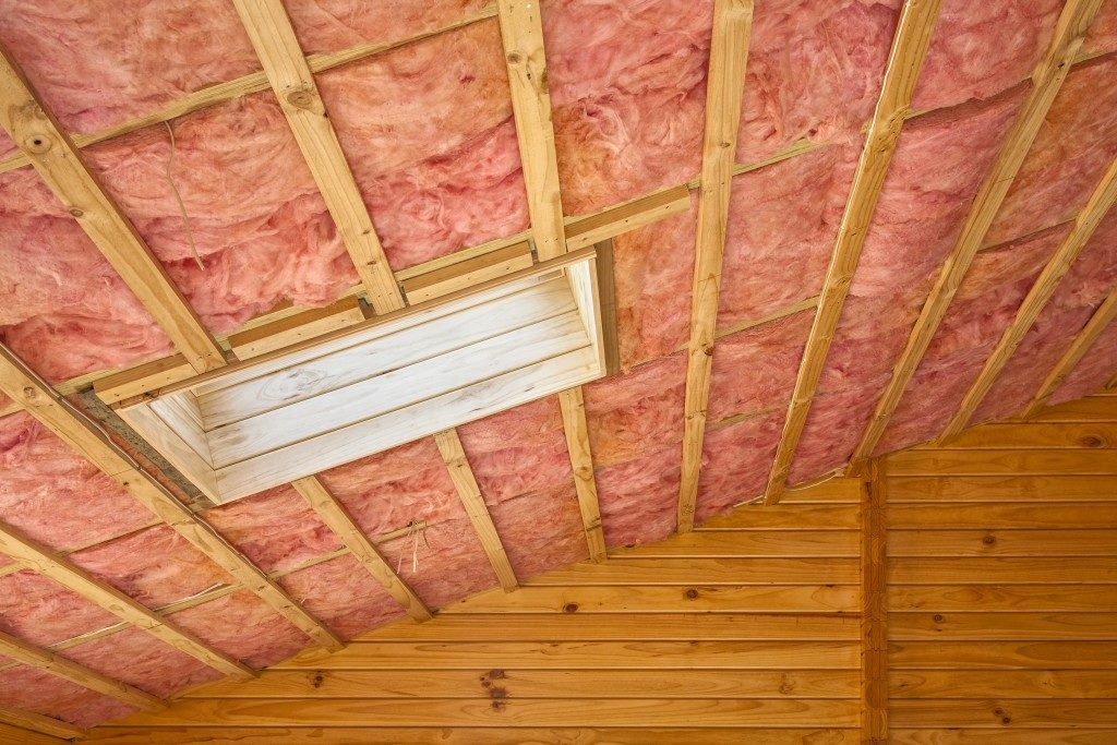 Fibreglass insulation installed in the sloping ceiling of a timber house.