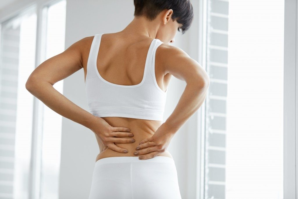 woman experiencing pain in her lower back