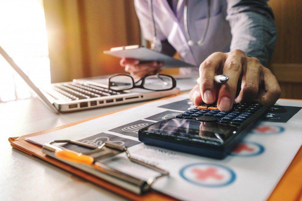 doctor computing a medical bill