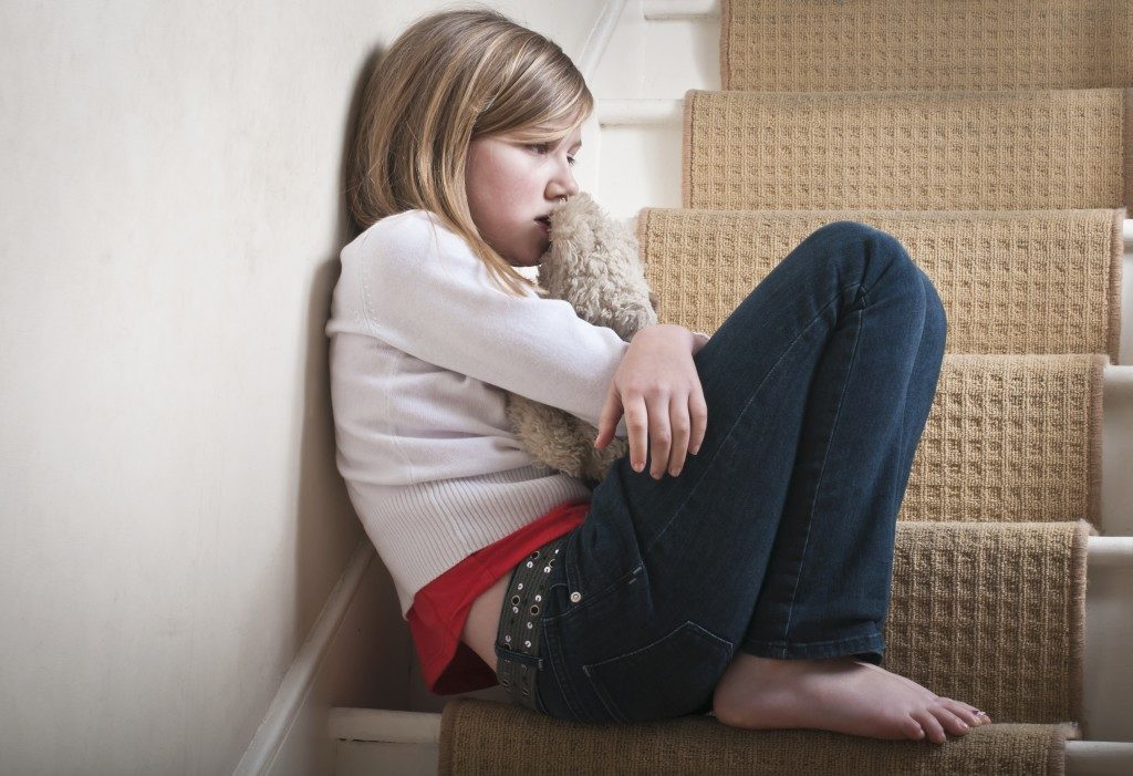 girl child hugging her stuff toy while sitting on a stair