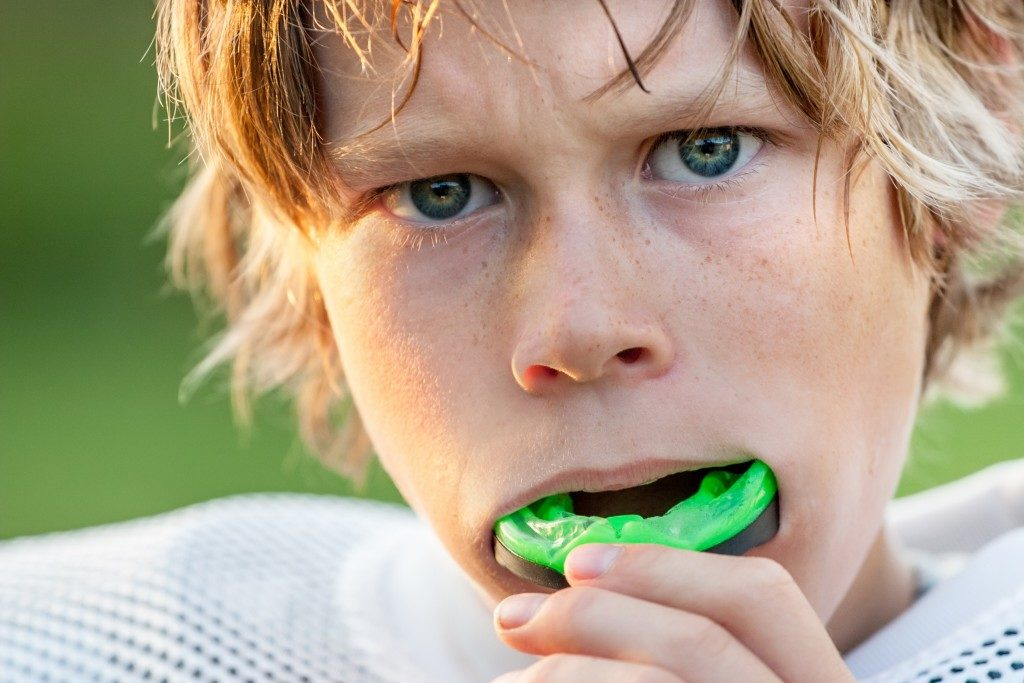 close up photo of a kid wearing mouth guard