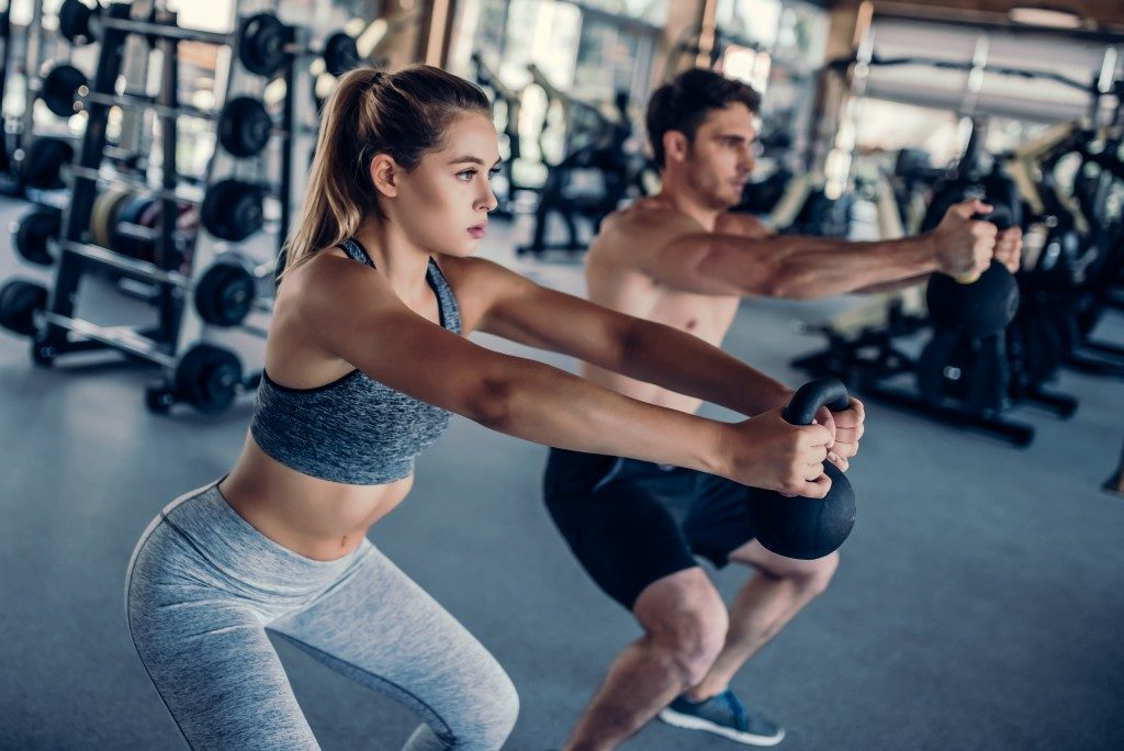 Man and woman lifting weights at the gym
