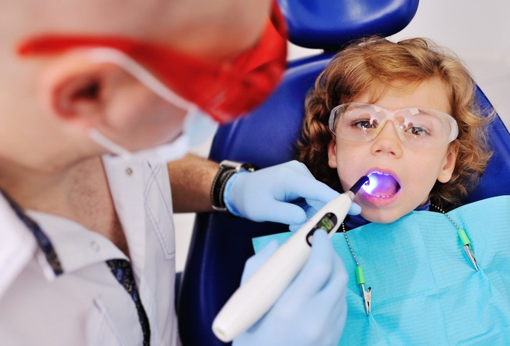Little boy having his teeth checked by the dentist