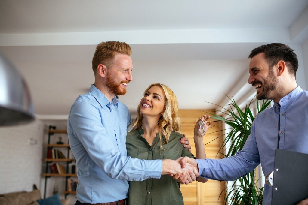 Couple shaking hands with agent