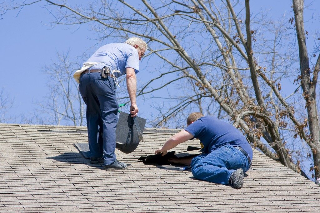 Two men fixing roof damage