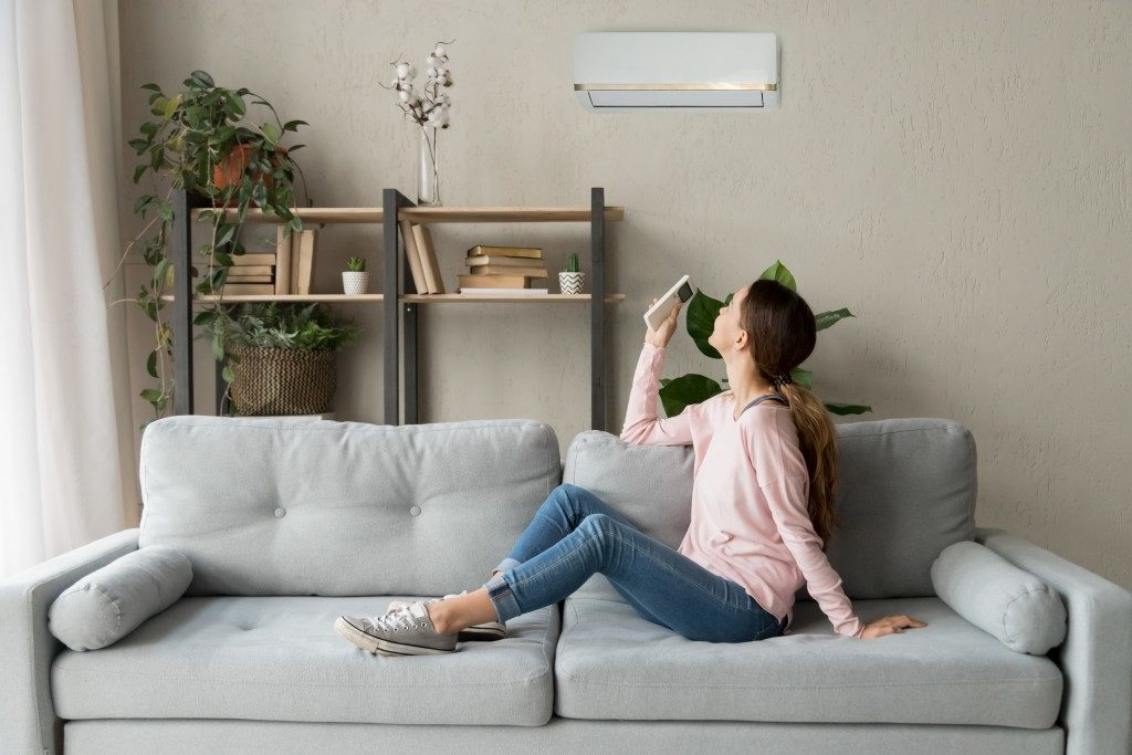 woman in sofa adjusting the aircon's temperature