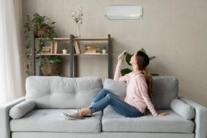 woman in sofa adjusting the aircon's temperature