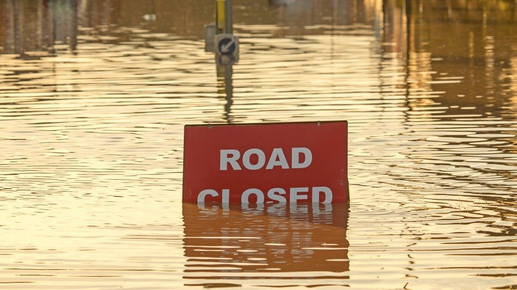 A 'Road Closed' sign partially covered in flood water lit by the evening sun