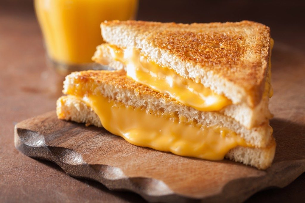 Two grilled cheese sandwiches on wooden platter with orange juice