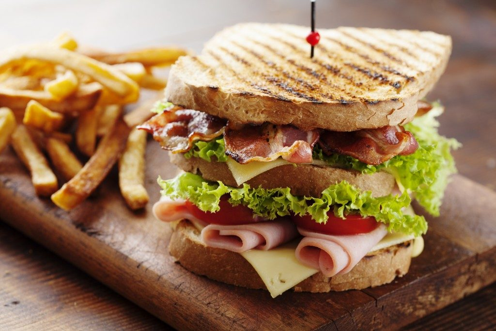 Club sandwich with fries served on wood
