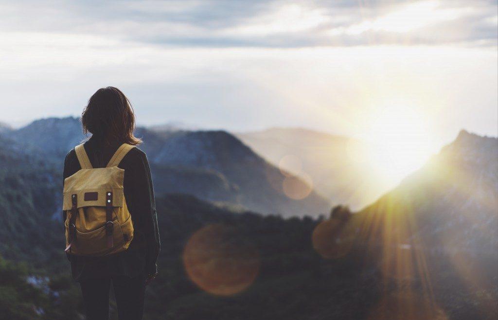 girl enjoying sunset on peak of a mountain