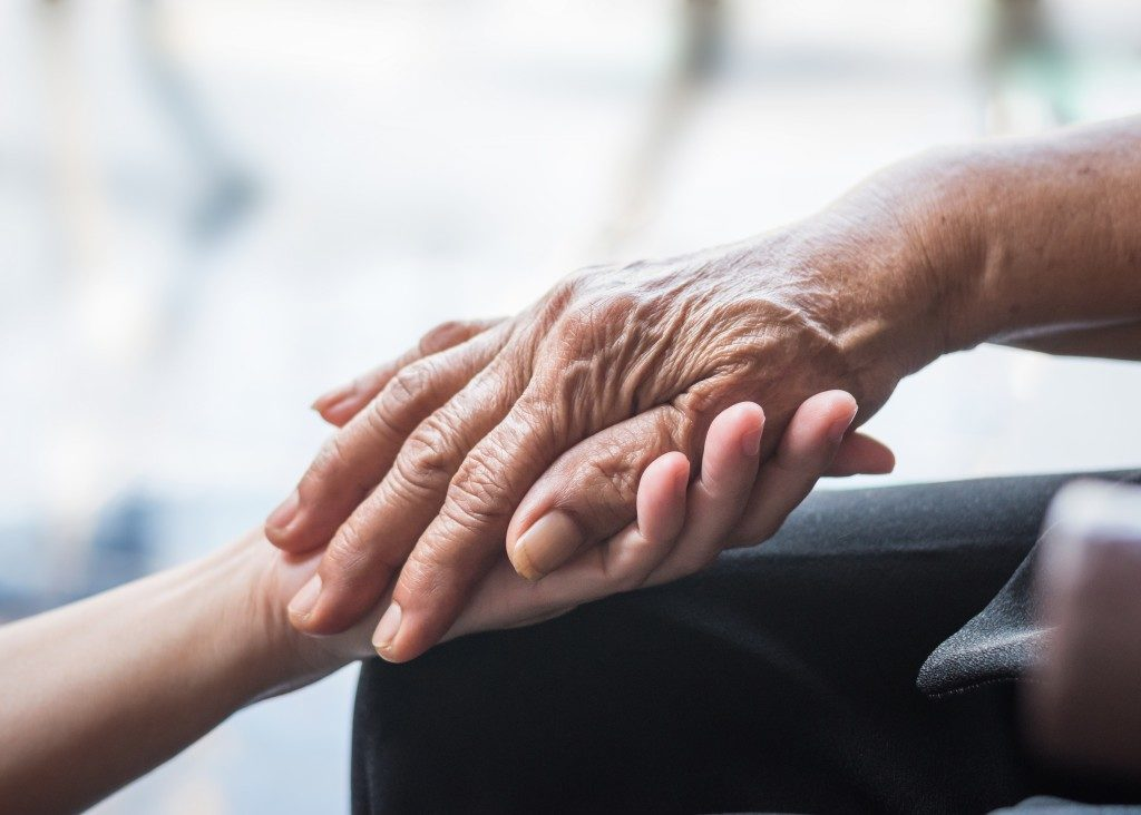 holding the hand of an elderly
