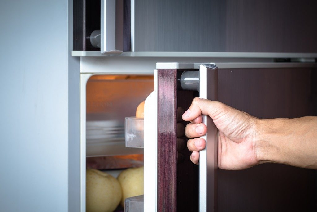 abstract hand of a young man is opening a refrigerator door