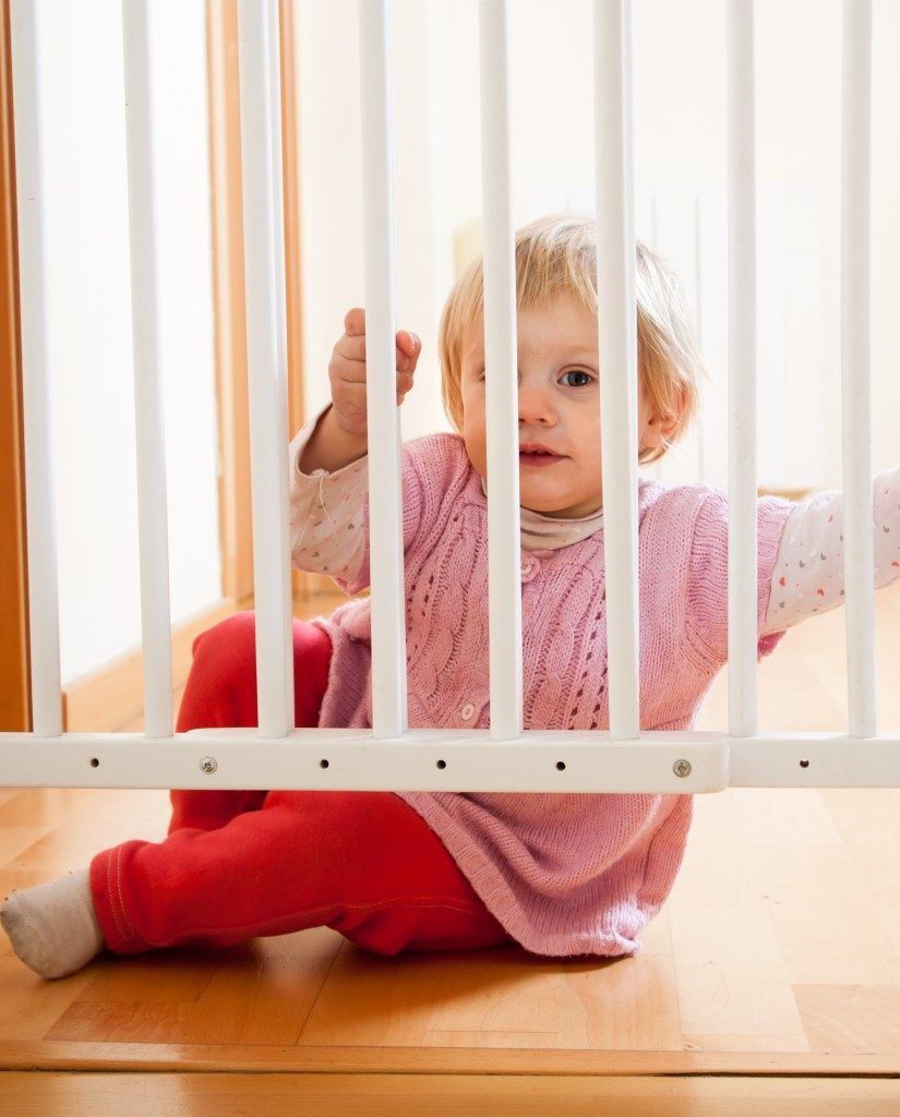 Small baby near safety gate of stairs