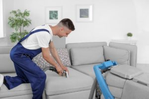 man cleaning couch