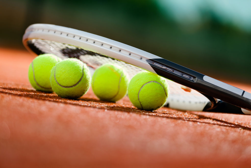 tennis balls under the racket