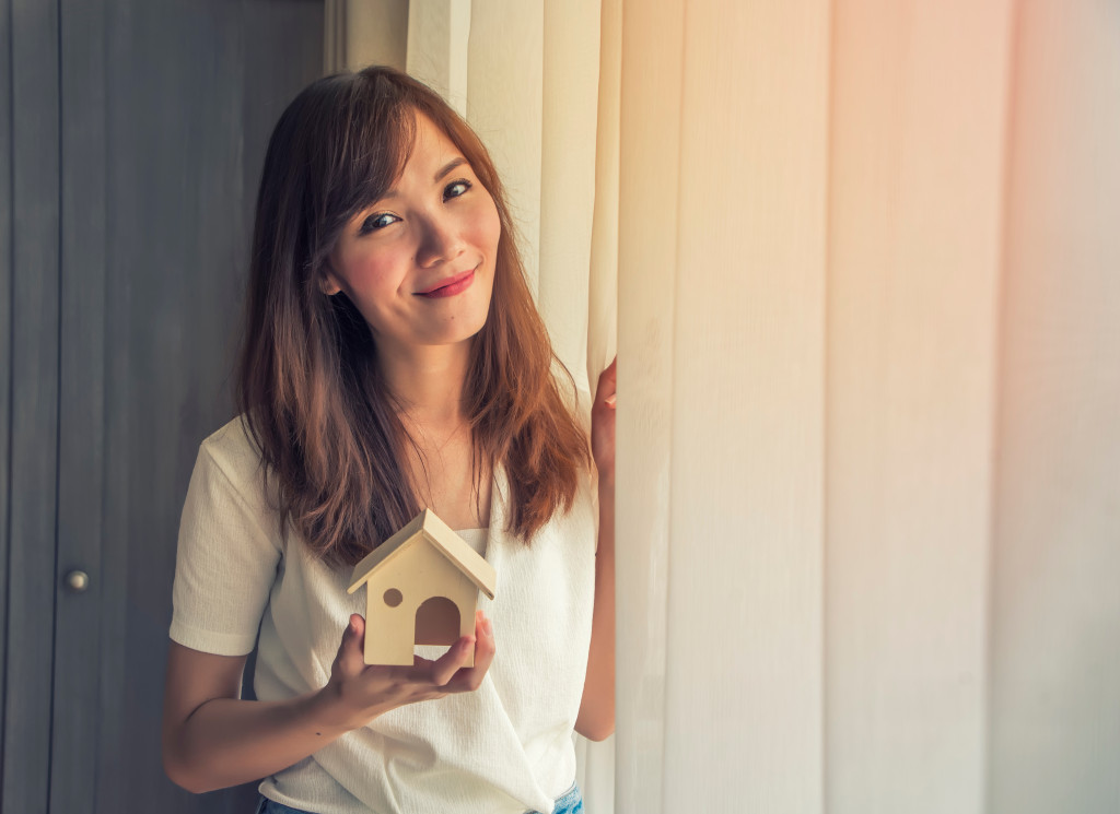 woman holding small house