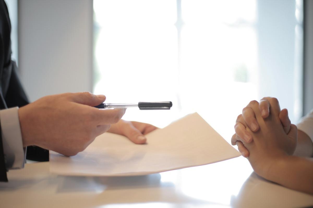 person handing over a pen